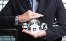 Man holding a car, house and family in a bubble in his hands