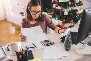 woman with paper and calculator with winter holiday decorations
