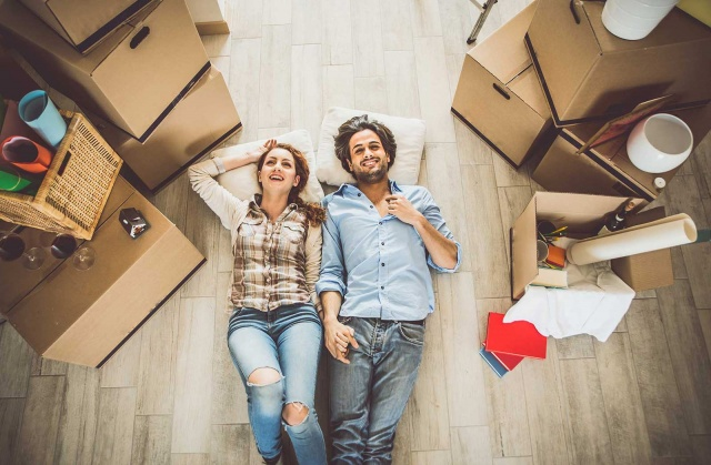 Young couple laying down and holding hands on wood floors surrounded by moving boxes.